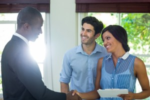 15255672-happy-couple-shaking-hands-with-real-estate-agent